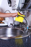 Cleaning the kitchen sink with sponge Royalty Free Stock Image