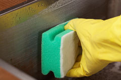 Cleaning kitchen sink. Cleaning a kitchen sink using cleaning sponge and cleaner stock images
