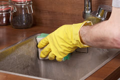 Cleaning kitchen sink. Cleaning a kitchen sink using cleaning sponge and cleaner stock photography