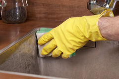 Cleaning kitchen sink. Cleaning a kitchen sink using cleaning sponge and cleaner royalty free stock photos