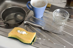 Cleaning A Kitchen. Sponge with a cleaner on top next to a metal kitchen sink, closeup shot with selective focus royalty free stock photo