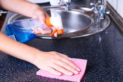 Cleaning kitchen with spray and sponge Stock Photos