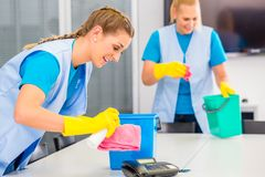Cleaning ladies working in office. Commercial cleaning crew ladies working as team in office stock photos