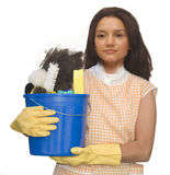 Cleaning Lady. Wearing rubber gloves and an apron holding a bucket of cleaning supplies on a white background royalty free stock image