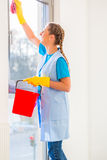 Cleaning lady with cloth. At window royalty free stock photography