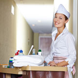 Cleaning lady doing housekeeping in hotel. Happy cleaning lady with cleaning cart doing housekeeping in hotel stock photos