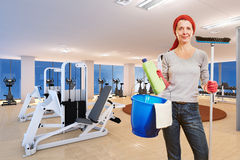 Cleaning lady in fitness center. Elderly cleaning lady with cleaning supplies standing in a fitness center stock photos