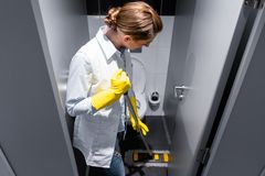 Cleaning lady or janitor mopping the floor in restroom. Cleaning the stall royalty free stock photos