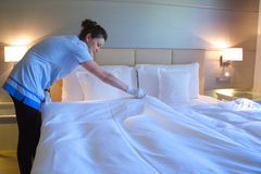 A cleaning lady is making the bed. In a hotel room royalty free stock images