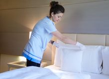 A cleaning lady is making up the bed Royalty Free Stock Photos