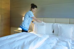 A cleaning lady is making up the bed Stock Photos