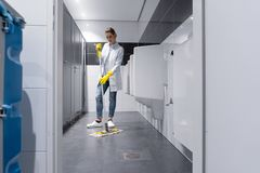 Cleaning lady mopping the floor in mens restroom. Or toilet royalty free stock photo