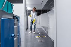 Cleaning lady mopping the floor in mens restroom stock photos