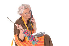 Cleaning lady on phone. Middle aged housewife, cleaning lady with curlers in hair chatting on phone, gossiping royalty free stock images
