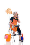 Cleaning lady on phone. Middle aged housewife, cleaning lady with curlers in hair chatting on phone, gossiping stock photos