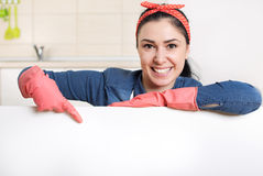 Cleaning lady pointing finger at blank board. Pretty young cleaning lady pointing finger at blank white board with kitchen in background royalty free stock images