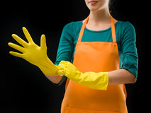 Cleaning lady putting on rubber gloves Royalty Free Stock Images