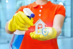 Cleaning lady shows qualitatively cleaned house. Cleaning lady shows qualitatively cleaned house on blurred background stock photo