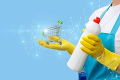 Cleaning lady shows the shopping cart and cleaning products . Cleaning lady shows the shopping cart and cleaning products on a blue background royalty free stock photography