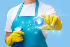 Cleaning lady shows sign of quality cleaning . Cleaning lady shows sign of quality cleaning on a blue background Royalty Free Stock Images
