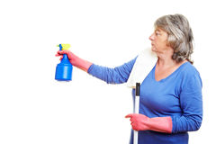 Cleaning lady with spray bottle. Elderly cleaning lady using a spray bottle royalty free stock image