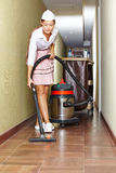 Cleaning lady with vacuum cleaner in hotel. Corridor royalty free stock images