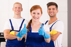 Cleaning lady wearing uniform. Cleaning lady and two men wearing uniforms and rubber gloves stock photo