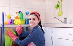 Cleaning lady wiping oven. Young pretty cleaning lady wiping oven and showing thumb up. Basin full of cleaning supplies on kitchen countertop stock photography
