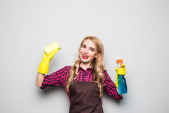 Cleaning lady. Woman cleaning scrubbing and polishing reaching and stretching with cleaning cloth and spray bottle. Caucasian girl standing isolated on white Stock Photos