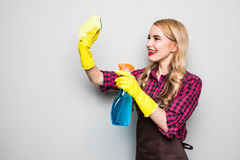 Cleaning lady. Woman cleaning scrubbing and polishing reaching and stretching with cleaning cloth and spray bottle. Royalty Free Stock Photography