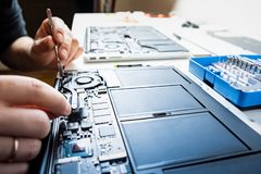 Cleaning a laptop at a professional service. Person performs regular service and changes thermal grease of modern portable computers, selective focus stock photos