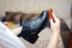 Cleaning leather boots with a shoe brush. stock image