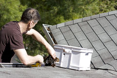 Cleaning leaves from the roof gutter Royalty Free Stock Images