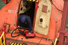 Cleaning the life boat with vacuum cleaner - funny royalty free stock photos
