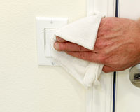 Cleaning a Light Switch. Hand cleaning a white home kitchen flat panel light switch with a white cotton cloth dust rag as part of regular housecleaning chores Royalty Free Stock Photos