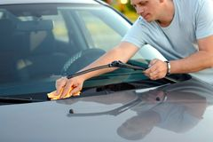 Cleaning like a professional- man cleaning his car with a microf. Iber cloth outdoors Royalty Free Stock Photo