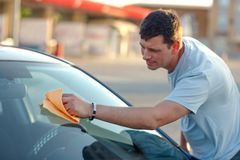 Cleaning like a professional-smiling man cleaning his car with a. Cleaning like a professional-smiling young man cleaning his car with a microfiber cloth Royalty Free Stock Photos