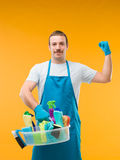 Cleaning man showing his biceps. Happy janitor holding cleaning supplies and showing his arm muscles Stock Photography