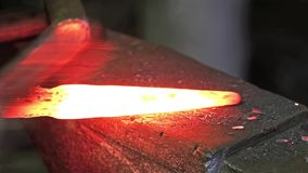 Cleaning of metal part with a metal brush in the blacksmith workshop stock video footage