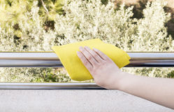 Cleaning metal Railing with a yellow cloth Stock Images