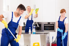 Cleaning of modern kitchen. Focused co-workers are cleaning modern kitchen royalty free stock photo