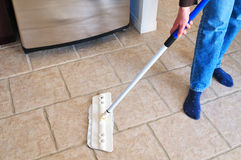 Cleaning with a mop. Close-up picture of woman's hand holding a mop cleaning kitchen floor Royalty Free Stock Image