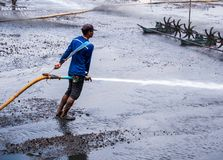 Cleaning the mud at the bottom of pond. CHACHOENGSAO THAILAND - JULY 13 : Unidentified men control high pressure water jet nozzle to clean the mud at the bottom royalty free stock photos