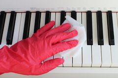 Cleaning a musical instrument to eliminate germs,Covid-19. Female hands in protective gloves cleaning the piano keys