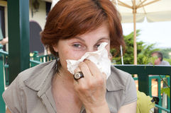 Cleaning nose. Mature senior lady is cleaning her nose with the napkin Stock Photo