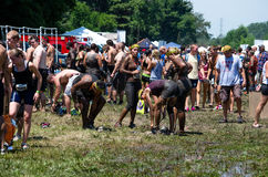 Cleaning off the mud. A group of muddy people wait in line to use outdoor showers at the 2012 mudathlon in northwest Indiana Royalty Free Stock Photography