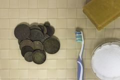 Cleaning old coins found by a metal detector royalty free stock photos