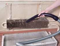 Cleaning the old radiator with a vacuum cleaner. Dusty heating system in the apartment Royalty Free Stock Photography