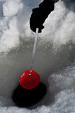 Cleaning out a hole for ice fishing Royalty Free Stock Photo