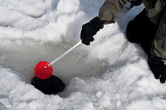 Cleaning out a hole for ice fishing Royalty Free Stock Image